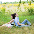 Portrait of a boy and a girl sitting on the grass in a field, ne — Stock Photo #39924435