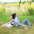 Portrait of a boy and a girl sitting on the grass in a field, ne — Stock Photo