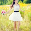 Girl in white dress with a bouquet of flowers and swirls in a fi — Stock Photo