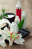 Skincare concept: white lily flowers with bottles of creams/loti — Stock Photo