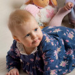 Cute baby girl playing with toys in nursery/daycare - Stock Photo