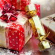 Christmas gift boxes and cracker on snowflakes and bokeh backgro — Stock Photo