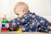Little girl playing with stalking toy pyramid — Stock Photo