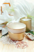 Moisturizing face cream with candle and white lily flowers, clos — Stock Photo