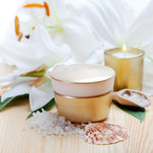 Face care and spa concept - face cream and lily flowers, closeup — Stock Photo