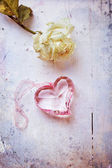 Pink glass heart with dried rose, aged stylized photo — Stock Photo