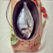 Fresh dorada fish in a stewing dish prepared for baking, with to — Stock Photo #46999311