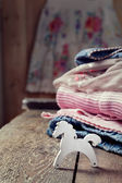 Various girls clothes on an old wooden table and a small toy woo — Stok fotoğraf