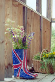 Wild flowers in Union Jack rubber boots-wellies on a country hou — Stock Photo