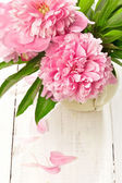 Pink peonies in retro vase on wooden table, closeup shot — Stock Photo