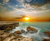 Sea cliffs and sunset over the sea — Stock Photo