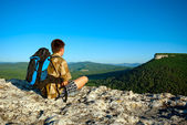 Young man with backpack sits — Stock Photo
