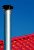 Chimney on a background of red roof and blue sky — Stock Photo