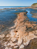 Kimmeridge Bay seascape with rock ledges extending out to sea on — Stock Photo