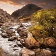Waterfall in mountains with moody dramatic mountain sunset lands — Stock Photo