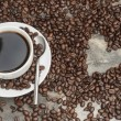Black coffee surrounded by beans with heart shaped hole, coffee  — Stock Photo