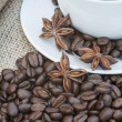 Stock Photo: Close up of coffe cup and saucer surrounded by beans on hessian