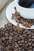 Close up of coffe cup and saucer surrounded by beans on hessian — Stock Photo