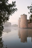 Stunning moat and castle in Autumn Fall sunrise with mist over m — Stock Photo
