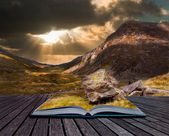 Moody dramatic mountain sunset landscape in pages of book — Stock Photo