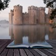 Stunning moat and castle in Autumn Fall sunrise with mist over m - Stock Photo