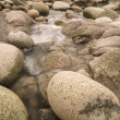 Water worn ancient rocks detail on secluded beach — Stock Photo #23988567