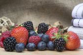 Fresh Summer berries in rustic kitchen setting — Stock Photo