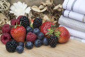 Fresh Summer berries in rustic kitchen setting — Stock Photo
