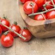 Fresh cherry tomatoes in rustic vintage wooden bowl — Stock Photo