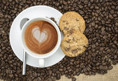 Cup of coffee with heart shape in foam on hessian background — Stock Photo