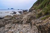 Rocky shore y brisons rock en distancia en cabo cornwall — Foto de Stock