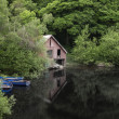 Stock Photo: Derelict old retro boathouse and rowing boats hidden in forest l