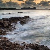 Stunning landscape dawn sunrise with rocky coastline and long exp — Stock Photo