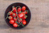 Beautiful fresh Perino snacking tomatoes in bowl in rustic setti — Stock Photo