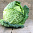 Fresh Savoy Cabbage on wooden background — Stock Photo