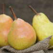 Fresh juicy pears in rustic wooden setting — Stock Photo
