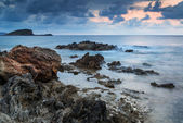 Landscape seascape of jagged and rugged rocks on coastline with — Stock Photo