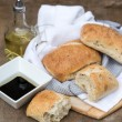 Olive bread rollis in rustic kitchen setting with utensils — Stock Photo