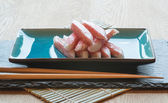 Fresh raw sushi crabsticks on plate with chopsticks — Stock Photo