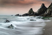 Landscape seascape of jagged and rugged rocks on coastline with — 图库照片