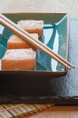 Fresh sushi salmon cream cheese parcels on plate with chopsticks — Stock Photo