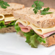 Fresh ham and cheese on white sandwich in rustic kitchen setting — Stock Photo #36031391