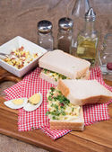 Fresh egg and bacn on white sandwich in rustic kitchen setting — Stock Photo