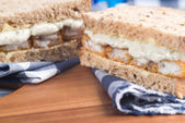 Fresh fish finger sandwich on wholegrain in rustic kitchen setti — Stock Photo