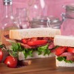Fresh BLT on white sandwich in rustic kitchen setting — Stock Photo #37602865