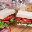 Fresh BLT on white sandwich in rustic kitchen setting — Stock Photo