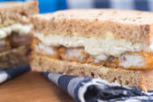 Fresh fish finger sandwich on wholegrain in rustic kitchen setti — Stockfoto