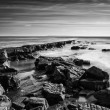 Beautiful black and white landscape of rocky shore at sunset — Stock Photo