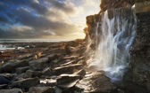 Beautiful landscape image waterfall flowing into rocks on beach  — Stock Photo
