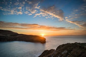 Beautiful vibrant sunrise over rocky coastline — Stock Photo